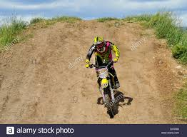 motocross bike photos a motocross bike rider riding down a hill on a gravel track stock