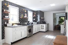 black backsplash in kitchen white kitchen with gray quartz countertops and glossy black