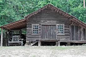 an old log cabin with an attached one car garage and a dilapidated