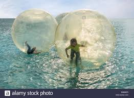 big plastic balloons children inside plastic balloons on the water stock photo