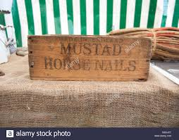 a branded old wooden box of horse shoe nails on a hessian cloth