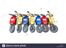 seven scooters in blue yellow and red colors parked isolated on