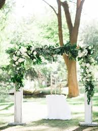 white wood ceremony arch with green garland wedding