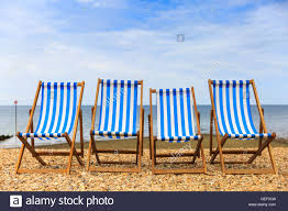 Chairs On A Beach Row Of Four Empty Deck Chairs On A Pebble Beach On The Sunny