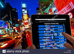New York City Time Square Map by Hands Holding Ipad Tablet Computer At Dusk In Times Square