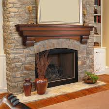 grey stone fireplace with brown wooden mantel shelf and black fire