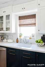 navy lower kitchen cabinets with long brass pulls transitional