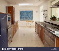cream travertine flooring in large modern galley kitchen with hob