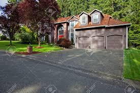big siding house with brick arch porch three car garage tile