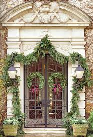 25 quick easy holiday decoration ideas sarah sarna outdoor decorating ideas christmas garlands frame the front door of this handsome house via