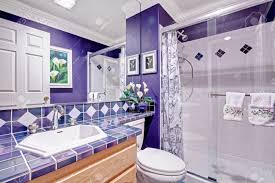 bright purple bathroom with tile wall trim and glass door shower