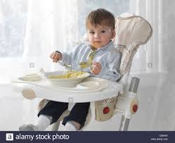 High Sitting Chair One And A Half Year Old Boy Sitting In A High Chair And Eating