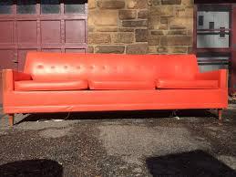long modern orange vinyl sleeper sofa with tapered legs