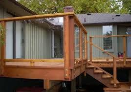 high level wooden deck with glass deck railing glass deck