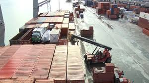 forklift tractor moving metal shipping containers in harbor stock