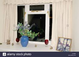 windowsill with vase of silk flowers and ornaments stock photo