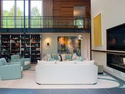 white sofa high ceiling area rug glass panel railing catwalk gray