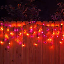 hang purple and orange icicle lights on black wire from the roof