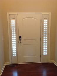 white front door with slim sidelights and blind treatment
