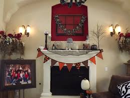 mini white halloween mantle decorations under red wall with