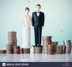 cake figurines up of wedding cake figurines on stacks of coins stock photo