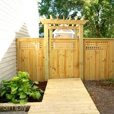 a beautiful fence and gate with an arbor simply swider blog
