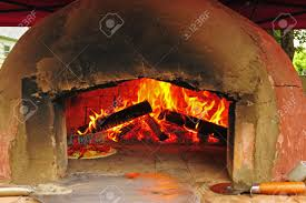 pizza cooking in the oven next to an open flame of a wood fire