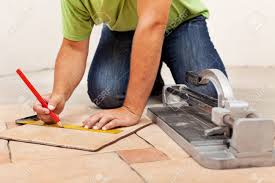 Laying Ceramic Floor Tile Worker Laying Ceramic Floor Tiles Measuring And Marking