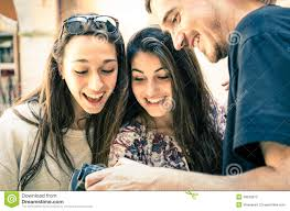 handsome boy shows pictures to beautiful girls stock photos