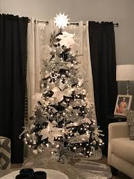 black christmas tree with silver and white decorations decorated