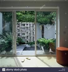Glass Patio Door View Through Glass Patio Doors To Courtyard Garden With Wall Stock