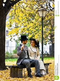old fashioned dressed couple on a park bench in fall stock images