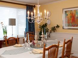 a low hanging crystal chandelier hangs above a dining room table