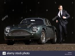 aston martin sports car man running beside db4 sports car by aston martin stock photo