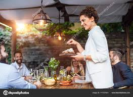 dinner host woman dinner party host serving food to her friends stock photo