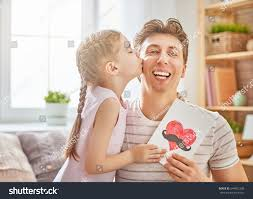 girls kissing in bed happy fathers day child daughter congratulates stock photo