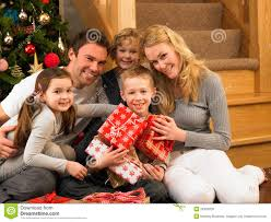 family with gifts in front of christmas tree stock photo image