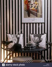 black patterned cushions checked boxes and hat on black metal seat with urn patterned