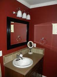 red bathroom dark red walls dark wood trimmed mirror beige tile