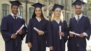 academic regalia graduates in academic regalia holding diplomas putting