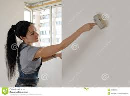 attractive woman painting a house wall stock photography image
