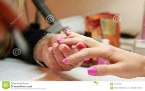 nail technician painting top coat onto customers pink nails stock