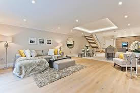 large living room basement with white wall and ceiling grey sofa