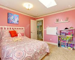 gentle girls bedroom with white bed and pink walls view of board gentle girls bedroom with white bed and pink walls view of board on the wall and