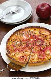baked apple rose tart with custard on black background stock photo