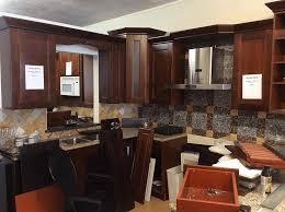 dark cherry kitchen cabinets grey plain countertop wood parquet flooring metal sink and faucet