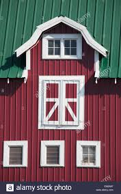 red barn with white trim and green roof alberta canada stock