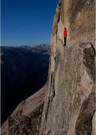 narrow picture ledge rock climber standing on a narrow ledge along the face of a sheer