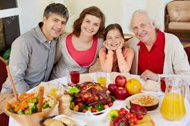 portrait of happy family sitting at festive table on thanksgiving