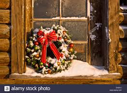 decorated christmas wreath sits in windowsill a rustic